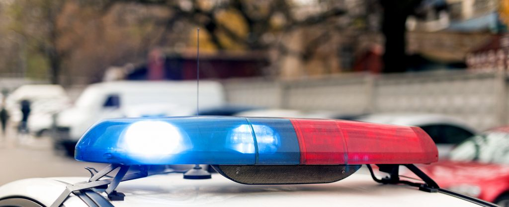 Roof of a poliñe patrol car with flashing blue and red lights, sirens and antennas.